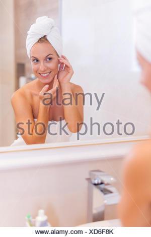 Femme à la réflexion elle-même dans le miroir après la douche. Debica, Pologne Banque D'Images