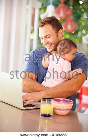 Père Holding Baby et faire collation tout en utilisant un ordinateur portable Banque D'Images