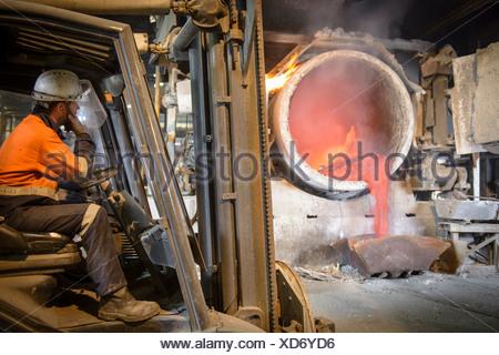 La surveillance des travailleurs de l'aluminium en fusion dans le moule en cours Banque D'Images