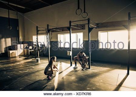Entraîneur féminin parler aux clients masculins in gymnasium Banque D'Images