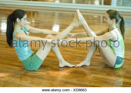 Deux jeunes femmes s'aidant mutuellement à étirer, side view Banque D'Images