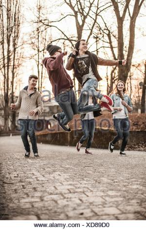 Cinq adolescents de jouer, sauter dans park Banque D'Images