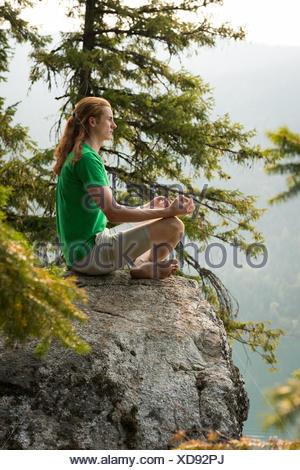 Fit l'homme assis en posture de méditation sur le bord d'un rocher Banque D'Images
