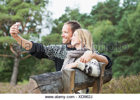 Couple sur banc de la photographier eux-mêmes Banque D'Images