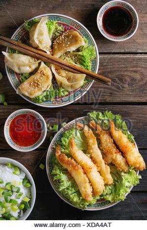 Poêlée de Crevettes tempura et les gyozas potstickers sur laitue salade avec les sauces et le riz. Servi dans la Chine traditionnelle avec des baguettes sur la plaque ancienne en bois Banque D'Images