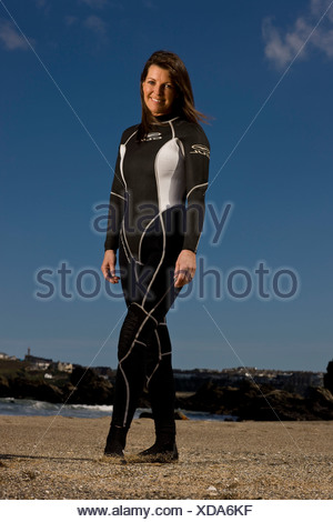Femme surfer standing on beach in wetsuit, smiling Banque D'Images