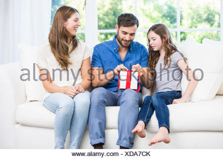 Cadeau d'ouverture de l'homme, assis sur un canapé avec la famille Banque D'Images
