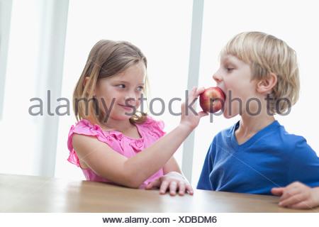 Les enfants mangeant apple en cuisine Banque D'Images