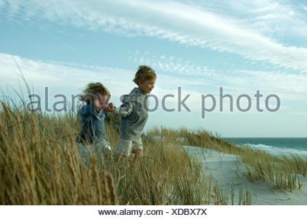Garçon et fille courir à travers dune grass, holding hands Banque D'Images