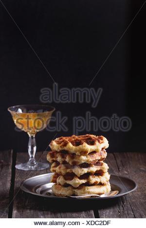 Plaque de métal avec des gaufres belges avec sirop d'orange dans un vase à fond. Plus de vieille table en bois. Style rustique foncé. Banque D'Images