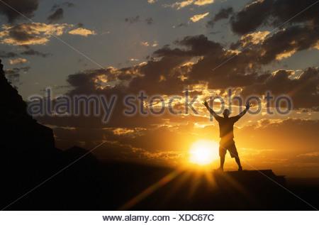 La figure masculine with arms outstretched standing avec coucher du soleil en arrière-plan Banque D'Images