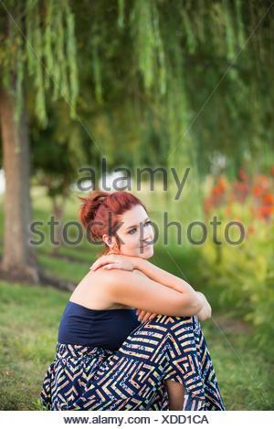 Une femme assise sous un saule pleureur. Banque D'Images