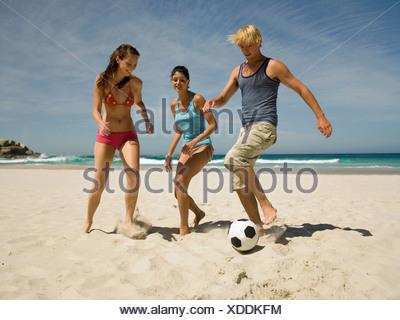 Les gens jouent au football sur la plage Banque D'Images