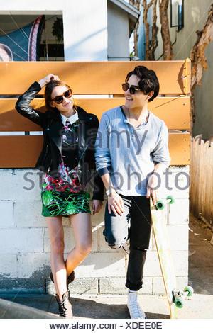 Jeune couple à l'extérieur, young man holding skateboard