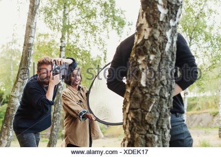 Photographier amis man leaning on tree trunk in forest Banque D'Images