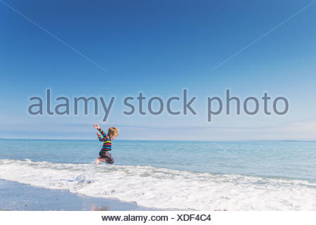 Boy jumping in surf Banque D'Images