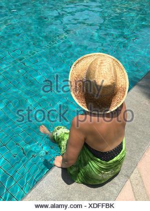 Femme assise avec pieds en piscine Banque D'Images