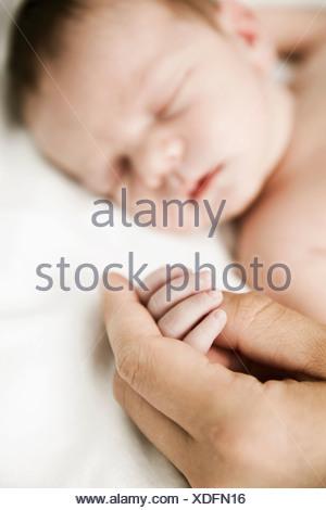 La main de son père fils nouveau-né sommeil Banque D'Images