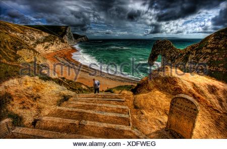 Unven étapes menant à Durdle Door, Dorset. L'eau blanche sur beach à partir de débris d'algues archway rock Banque D'Images