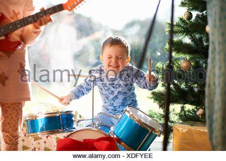 Garçon et sœur jouant toy kit de batterie et guitare le jour de Noël Banque D'Images