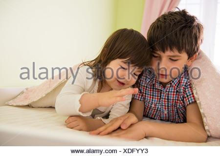 Jeu de frère et sœur au lit Banque D'Images