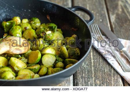 Poêlée de choux de Bruxelles dans la poêle en fonte sur table en bois Banque D'Images