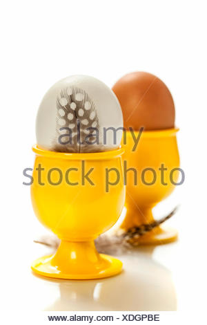 Oeufs en jaune eggcups isolated on white Banque D'Images