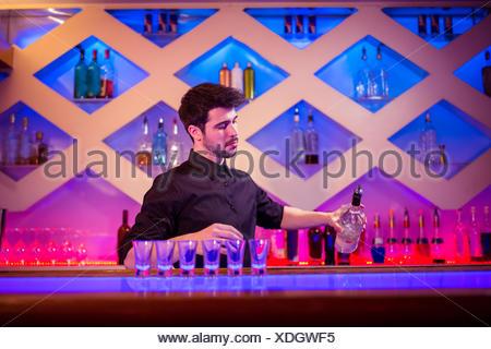 Bartender pouring alcool en verre au comptoir