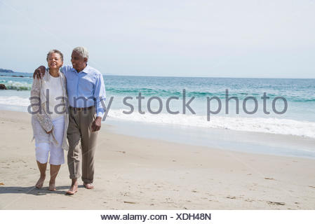 La haute couple waking together on beach, smiling Banque D'Images