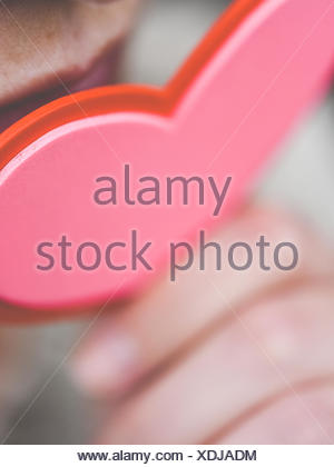 Femme tenant un cœur de papier près de sa bouche Banque D'Images