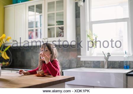 Fille assise dans la cuisine manger du chocolat dessert et lécher les doigts Banque D'Images
