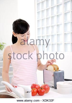 Jeune femme de mettre les tranches de pain grillé dans un four grille-pain tomates de côté Banque D'Images