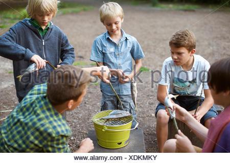 Les jeunes garçons Cuisiner les poissons sur le barbecue Banque D'Images