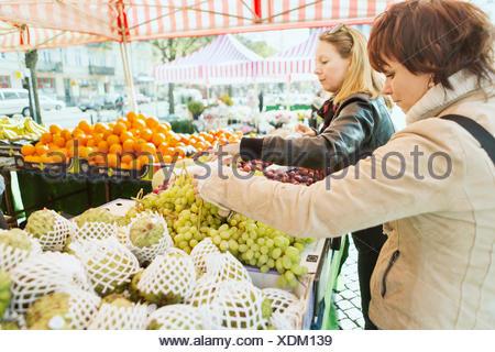 Vue de côté les femmes mûres fruits achat at market stall Banque D'Images