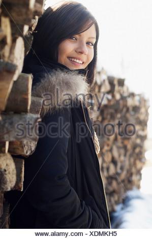 Portrait de jeune femme en face de pile de journaux Banque D'Images