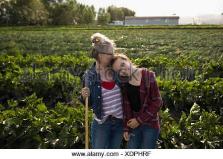 Portrait of smiling, tendre Mère agriculteur kissing fille en culture sur sunny farm Banque D'Images