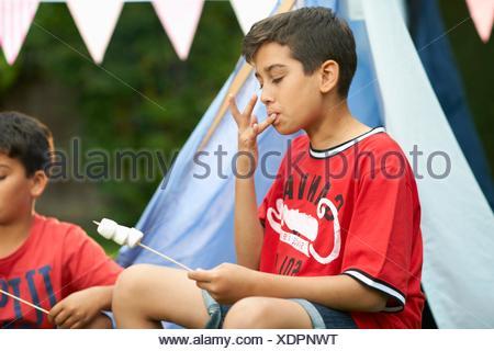 Deux frères de manger des guimauves grillées au jardin Banque D'Images