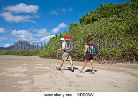 Un homme et une femme avec leur bébé en randonnée sur l'île de Hinchinbrook, Zoe Bay, Queensland, Australie. Banque D'Images
