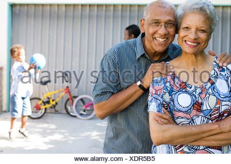 Couple standing in driveway avec les gens en arrière-plan Banque D'Images