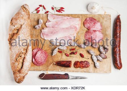 Ensemble de salami et de jambon servi avec du pain frais sur la vieille planche à découper en bois.