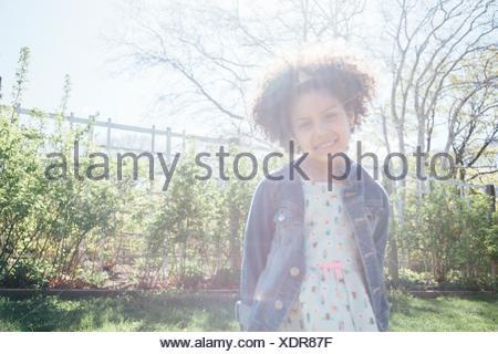 Vue de face de jeune fille dans la lumière du soleil, les mains derrière le dos, smiling at camera Banque D'Images