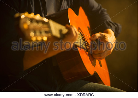 Close up of man playing acoustic guitar, studio shot Banque D'Images