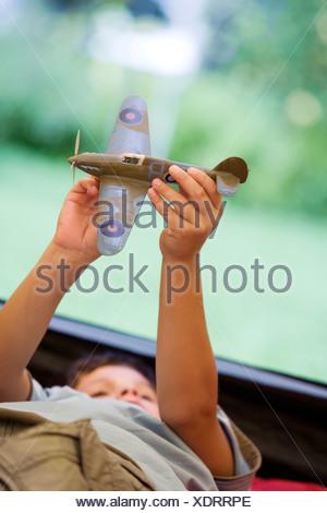 Boy 810 couché sur un sac de couchage à l'intérieur de tente sur jardin pelouse Playing with toy aero avion tilt Banque D'Images