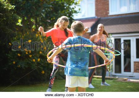 Femme mature avec fils et fille adolescente hula hooping in garden Banque D'Images
