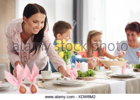 La femme et la famille Préparation Placez les paramètres à Pâques, table à manger Banque D'Images