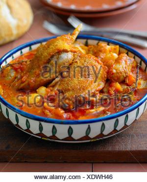 Cassoulet de canard, dans un plat coloré, sur une planche à découper - avec fiche Banque D'Images