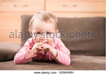 Baby Girl 18 mois portrait lying on sofa Banque D'Images