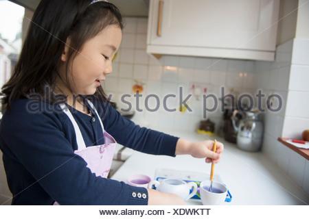 Jeune fille trempant le pinceau dans l'eau dans la cuisine bol Banque D'Images
