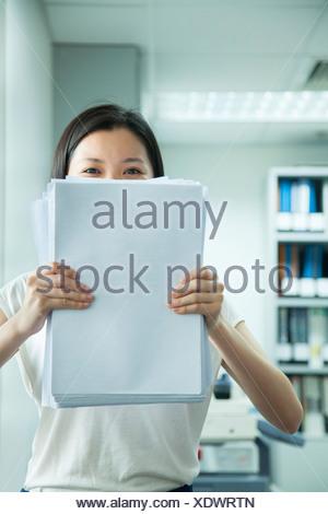 Businesswoman se cacher derrière le papier Banque D'Images