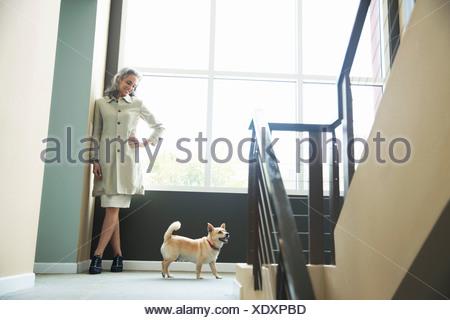Femme mature et chien de compagnie sur escalier Banque D'Images